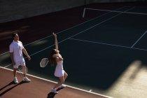 Вид сбоку на молодую кавказку и мужчину, играющего в теннис в солнечный день, служанку — стоковое фото