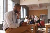 Vista laterale da vicino di un giovane afroamericano seduto su una scrivania usando un tablet e pensando in un ufficio creativo, con due colleghi che lavorano sullo sfondo — Foto stock