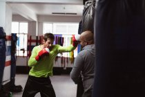Front view of a young Caucasian male boxer punching a punchbag held by a middle aged Caucasian male trainer in a boxing gym — Stock Photo