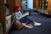 Бічний вид на молоду азіатську студентку, одягнену в тюрбан, яка читає книжку і навчається в бібліотеці. — стокове фото