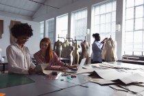 Vista frontale di una giovane studentessa afroamericana che tiene in mano un tablet e lo mostra a una giovane studentessa caucasica che usa un computer portatile in uno studio di moda, con uno studente di sesso maschile che lavora su una giacca sullo sfondo — Foto stock