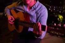 Frontansicht Mittelteil eines jungen kaukasischen Mannes, der während einer Session in einem Tonstudio sitzt und eine akustische Gitarre spielt — Stockfoto