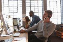 Seitenansicht eines jungen kaukasischen Mannes, der in einem kreativen Büro an einem Schreibtisch sitzt und mit einem Smartphone spricht, während zwei Kollegen auf einen Monitor schauen und im Hintergrund — Stockfoto