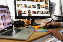 Gros plan des mains d'une femme assise à un bureau avec un ordinateur portable, un écran d'ordinateur à l'aide d'un stylet et une tablette graphique dans un bureau créatif — Photo de stock