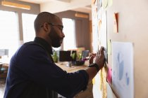 Side view close up of a young African American man writing notes on a wall during a team brainstorm session at a creative office — Stock Photo