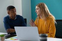 Nahaufnahme eines jungen afrikanisch-amerikanischen Mannes, der zuhört, und einer jungen kaukasischen Frau, die einen Laptop benutzt und miteinander spricht, an einem Schreibtisch im modernen Büro eines kreativen Unternehmens — Stockfoto