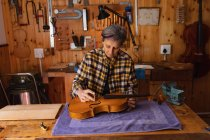 Front view of a senior Caucasian female luthier working on the body of a violin in her workshop with tools hanging up on the wall in the background — Stock Photo