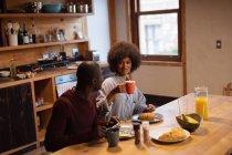 Vue de face d'une jeune femme souriante métissée et de son partenaire, un jeune Afro-Américain, mangeant, parlant et buvant du café assis à leur table de cuisine à la maison — Photo de stock