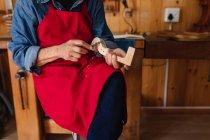 Vista frontal close up de luthier feminino trabalhando no pergaminho de um violino em sua oficina — Fotografia de Stock