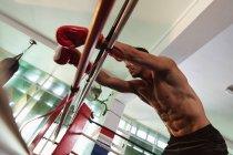 Вид сбоку на молодого кавказского боксера в боксёрском ринге, опирающегося на веревку — стоковое фото