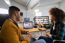 Вид сбоку на молодого человека смешанной расы и молодую женщину смешанной расы, сидящую за столом и смотрящую на экран компьютера и обсуждающую в творческом офисе — стоковое фото