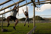 Front view of a young Caucasian man hanging from ropes on a climbing frame at an outdoor gym during a bootcamp training session, with a woman hanging from ropes in the background — Stock Photo