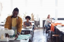 Vue de face d'un jeune étudiant afro-américain de mode utilisant une machine à coudre tout en travaillant sur un design dans un studio au collège de mode, avec d'autres étudiants au travail en arrière-plan — Photo de stock