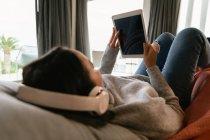 Через плечо юная брюнетка, лежащая на диване с поднятыми ногами, в наушниках и смотрящая планшетный компьютер — стоковое фото