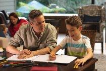 Передній погляд на чоловіка середнього віку, який допомагає своєму старшому сину виконати домашнє завдання, мати розмовляє з іншим сином на задньому плані. — стокове фото