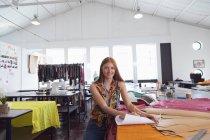 Porträt einer jungen kaukasischen Modestudentin, die in die Kamera lächelt, während sie in einem Atelier der Modehochschule an einem Design arbeitet — Stockfoto