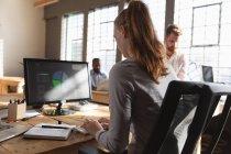 Rückseite Nahaufnahme einer jungen kaukasischen Frau, die am Schreibtisch sitzt und einen Computer in einem kreativen Büro benutzt, während im Hintergrund zwei männliche Kollegen sitzen und arbeiten — Stockfoto