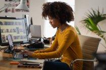 Вид сбоку на молодую расистку, сидящую за столом с ноутбуком в креативном офисе — стоковое фото