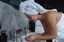 Vue de côté gros plan d'une jeune femme caucasienne souriante avec ses cheveux enveloppés dans une serviette se lavant le visage dans une salle de bain moderne — Photo de stock