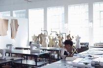 Вид сбоку молодой студентки-модницы смешанной расы, сидящей за столом, работающей над дизайном в студии при колледже моды с манекенами на заднем плане — стоковое фото