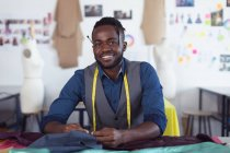 Portrait of a young African American male fashion student with a tape measure around his neck smiling to camera and working on a design in a studio at fashion college — Stock Photo