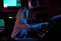 Vista lateral de perto de uma jovem engenheira de som caucasiana sentada e trabalhando em uma mesa de mistura em um estúdio de gravação — Fotografia de Stock