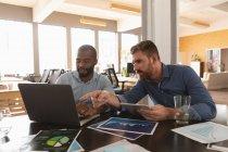 Nahaufnahme eines jungen afrikanisch-amerikanischen Mannes und eines jungen kaukasischen Mannes, die an einem Schreibtisch sitzen und einen Laptop benutzen, um Visuals anzusehen und in einem kreativen Büro miteinander zu reden — Stockfoto