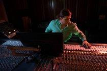 Frontansicht eines jungen kaukasischen männlichen Tontechnikers, der an einem Mischpult in einem Tonstudio sitzt und arbeitet. — Stockfoto