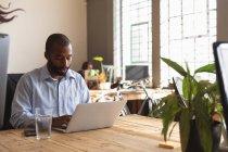 Вид спереди на молодого афроамериканца, сидящего за столом со стаканом воды, используя ноутбук в творческом офисе, на фоне коллеги, работающего на заднем плане — стоковое фото