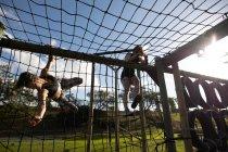 Вид спереди на двух молодых кавказских женщин, залезающих по сетям в кадр для скалолазания в открытом тренажерном зале во время тренировочного лагеря — стоковое фото