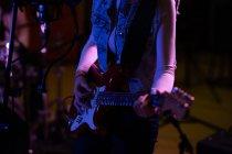 Сторона зору посередині жінки, яка грає на електричній гітарі під час сесії в студії звукозапису. — стокове фото