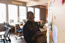 Вид спереди на молодого афроамериканца с планшетного компьютера, стоящего у доски настроения во время группового мозгового штурма в креативном офисе — стоковое фото