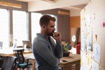 Seitenansicht eines jungen kaukasischen Mannes, der Notizen an einer Wand liest und während eines Team-Brainstormings in einem Kreativbüro denkt — Stockfoto