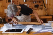 Front view of a senior Caucasian female luthier measuring the body of a violin on a workbench in her workshop, with a tablet computer in front of her and tools hanging up on the wall in the background — Stock Photo
