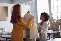Vista frontal de uma jovem negra caucasiana mista estudante de moda feminina trabalhando em um projeto em um estúdio na faculdade de moda — Fotografia de Stock