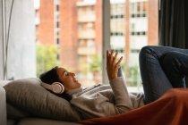 Vista laterale di una giovane donna bruna caucasica sorridente sdraiata su un divano con le gambe alzate, indossando cuffie e tenendo uno smartphone — Foto stock