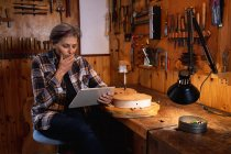 Front view of a senior Caucasian female luthier using a tablet computer with tools hanging up on the wall in the background — Stock Photo