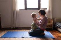 Боковой вид молодой кавказской матери, сидящей на полу и держащей своего ребенка, смотрящей друг на друга — стоковое фото