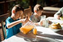 Vue de côté gros plan de deux pré adolescents garçons caucasiens assis à une table profitant d'un petit déjeuner familial dans un jardin — Photo de stock