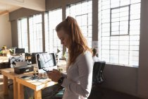 Vista lateral de cerca de una joven mujer caucásica de pie usando un teléfono inteligente en una oficina creativa con escritorios y computadoras en el fondo - foto de stock