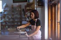 Вид сбоку молодой кавказской женщины-гончара, сидящей за рабочим столом перед окном, работающей с глиной на бандажном колесе в гончарной мастерской — стоковое фото