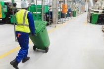 Vista posteriore da vicino di un giovane operaio afroamericano che fa scorrere un bidone verde attraverso un magazzino in uno stabilimento di trasformazione — Foto stock