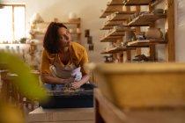 Вид на молодий Кавказький жіночий Поттер сидить і працює з глиною на гончарних колесо в гончарної студії, і дивлячись на бік посміхаючись, поки вона працює, з обладнанням на передньому плані — стокове фото