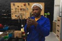 Передній план закрити вигляд молодого афроамериканського робітника фабрики, який оглядає обладнання в машинобудівному цеху, з обладнанням і інструментами на задньому плані — стокове фото