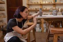 Вид сбоку на молодую кавказскую горшечницу, стоящую на коленях с глиняной фляжкой на столе и проверяющую ее — стоковое фото