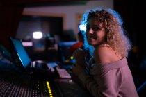 Зворотний бік зображення молодої кавказької жінки-звукоінженера, яка сидить і працює за змішувальним столом у студії звукозапису, звертаючись до камери посміхаючись — стокове фото