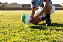 Front view low section of female rugby player kneeling on a rugby pitch and setting the ball on a tee for a place kick — Stock Photo