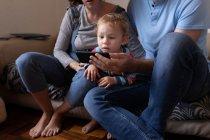 Vista frontal de cerca de un joven padre y madre caucásicos sentados en un sofá y usando un teléfono inteligente con su bebé - foto de stock