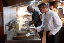 Vue latérale de près d'un chef caucasien d'âge moyen et jeune homme afro-américain du personnel de cuisine debout sur les friteuses dans une cuisine de restaurant — Photo de stock