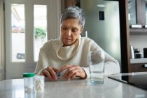 Vue de face gros plan d'une femme caucasienne mature aux cheveux gris court assise dans sa cuisine regardant ses médicaments, avec des bouteilles de pilules, une boîte à pilules hebdomadaire et un verre d'eau sur le comptoir à côté d'elle — Photo de stock